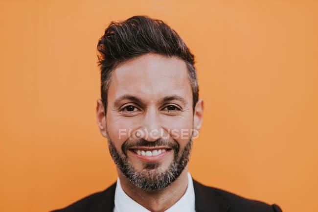 Adulto bell'uomo d'affari elegante in abito formale guardando la fotocamera vicino alla parete arancione — Foto stock