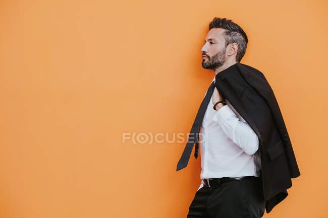 Вид сбоку взрослого красивого элегантного жизнерадостного бизнесмена в формальном костюме с рукой в кармане, отводящего взгляд в сторону у оранжевой стены на городской улице — стоковое фото