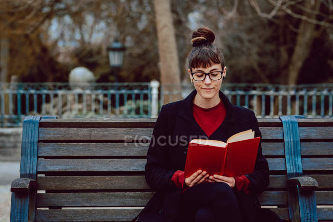 Young attractive elegant woman in eyeglasses reading book and sitting on bench in city garden — Stock Photo