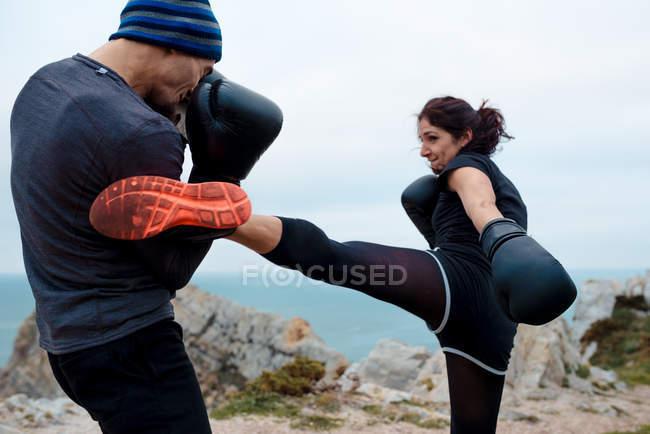Mann und Frau in Boxhandschuhen schlagen sich gegenseitig, während sie auf einer Klippe gegen Meer und Himmel stehen — Stockfoto