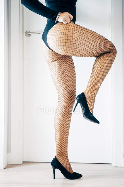 Jambes et les fesses parfaites de femme provocante portant body érotique et collants résille — Photo de stock