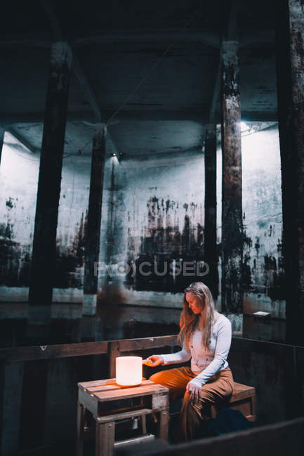 Young woman sitting near lights in dark building — Stock Photo