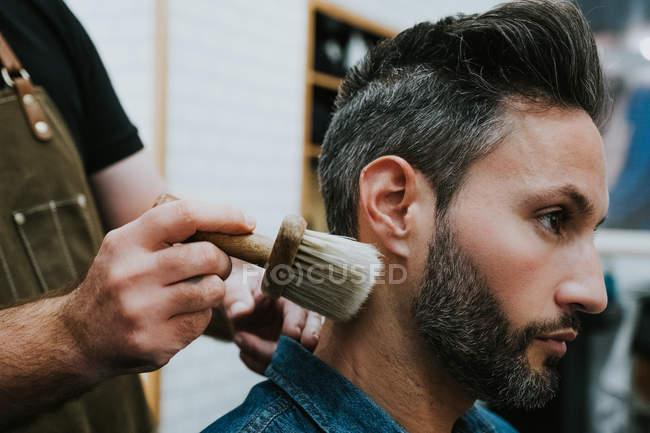 Vista laterale del barbiere con pennello vicino felice bello elegante maschio seduto in sedia in salone — Foto stock