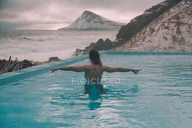 Back view of young woman with outstretched arms standing in water of pool near cliffs on coast and stormy sea — Stockfoto