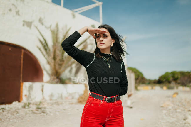 Young woman in trendy outfit covering eyes of sun while standing near white shabby house on street — Stock Photo