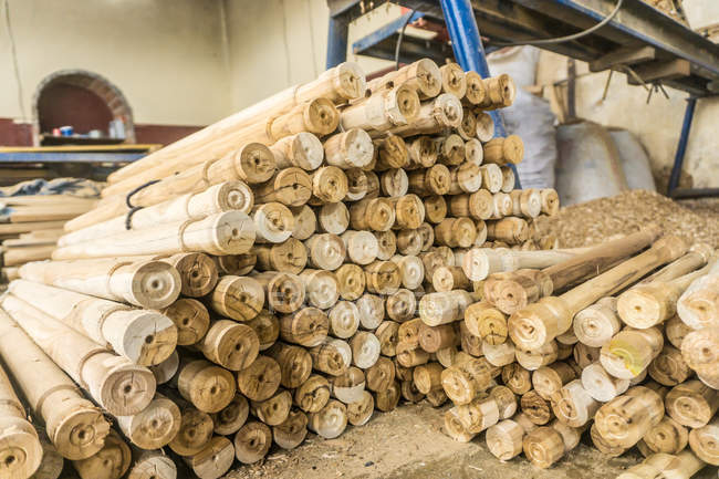 Pile of wooden sticks near sawdust and woodworking machine at workplace — Stock Photo