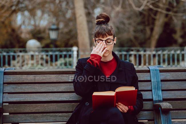 Молода елегантна жінка в окулярах читає книжку, сидячи на лавці в міському парку. — стокове фото