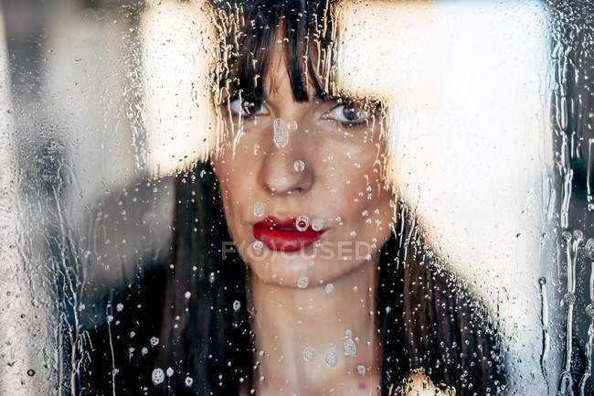 Attractive female with red lips kissing behind transparent glass — Stock Photo