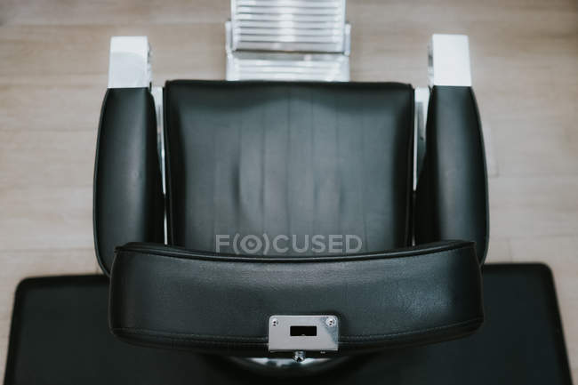 Modern leather chair in barbershop on blurred background — Stock Photo