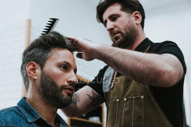 Знизу перукарня чіпляється за волосся вродливого стильного чоловіка, який сидить у перукарні. — стокове фото