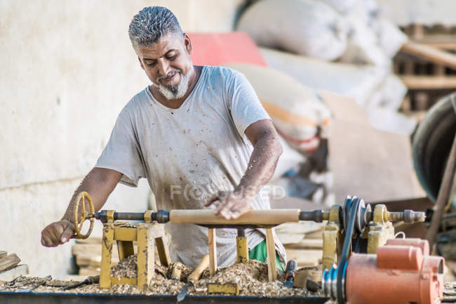 Lächelnder Mann mit Holzbearbeitungsmaschine am Arbeitsplatz — Stockfoto