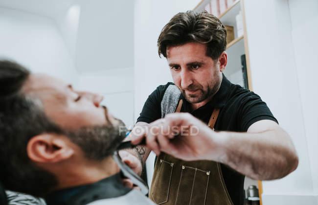 Парикмахер с расческой и стрижкой бороды мужчины, сидящего в парикмахерской на размытом фоне — стоковое фото