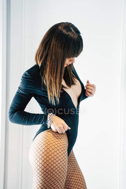 Seductive female in black bodysuit and and fishnet tights touching body and looking down — Stock Photo