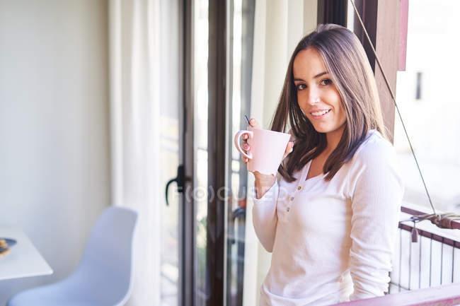 Улыбающаяся молодая женщина, держащая чашку возле окна дома и глядя в камеру — стоковое фото