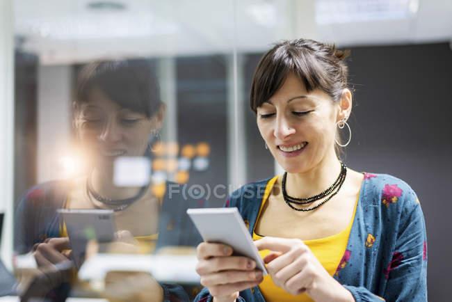 Sorridente gerente do sexo feminino usando smartphone enquanto estava perto da parede de vidro no escritório moderno — Fotografia de Stock