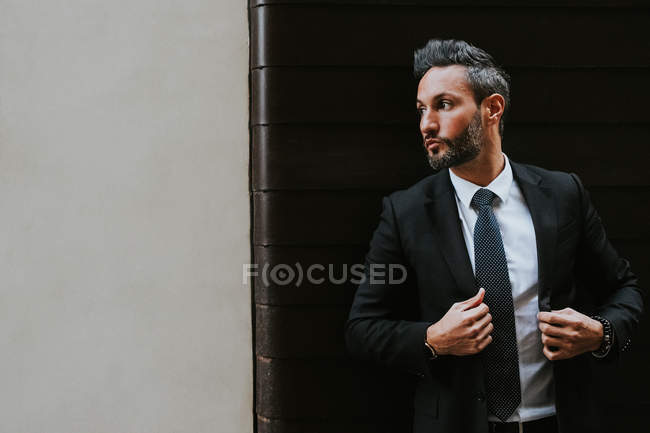 Adult handsome elegant businessman in formal suit looking away near wall — Stock Photo