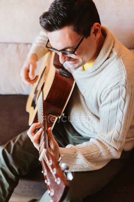 Lächelnder Mann mit Brille spielt daheim auf dem Sofa Gitarre — Stockfoto