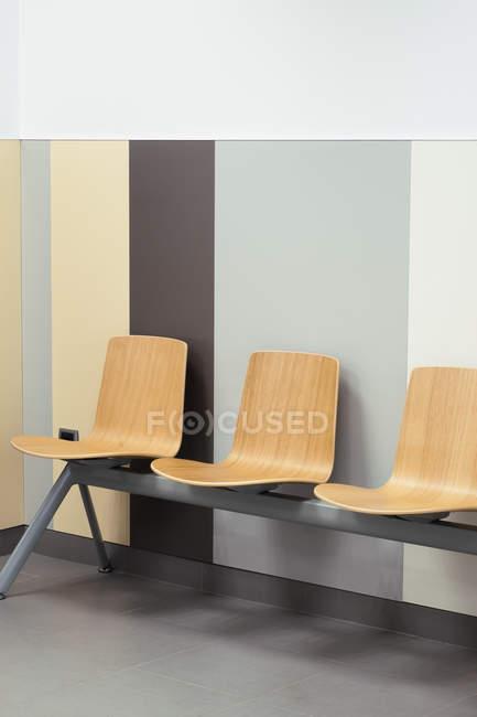 Rangée de chaises confortables près du mur élégamment peint dans la salle d'attente du lieu public — Photo de stock