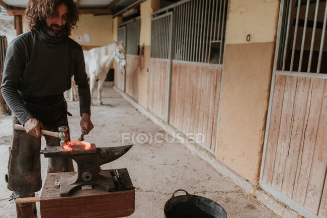 Adult farrier using hammer and tongs to forge hot horseshoe on portable anvil near stable on ranch — Stock Photo