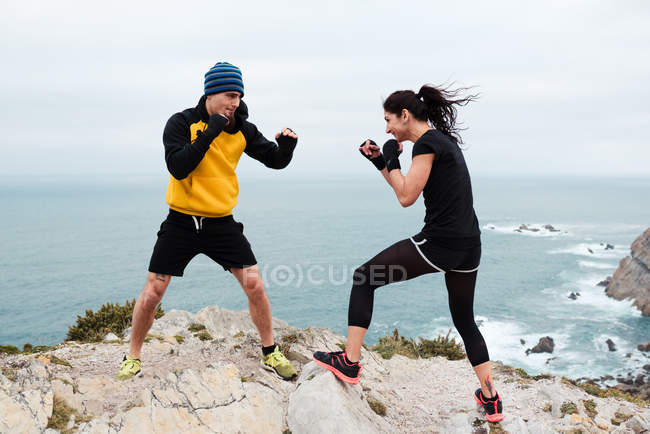 Man and woman in boxing gloves punching each other while standing on cliff against sea and sky — Stock Photo