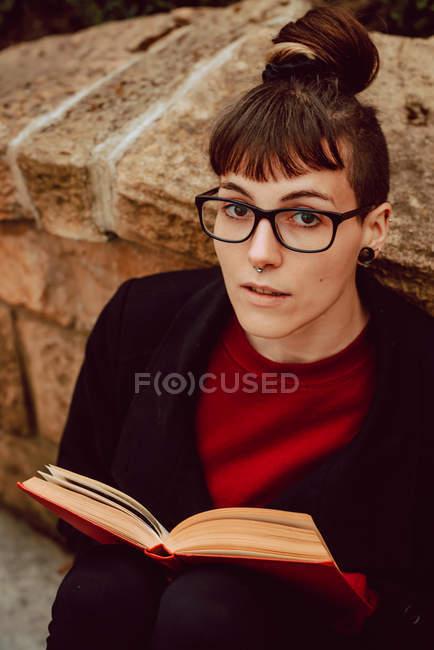 Jeune femme élégante avec des lunettes appuyées sur un mur de pierre avec un livre et regardant la caméra — Photo de stock