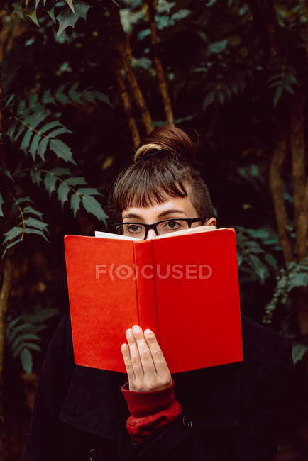 Young elegant woman in eyeglasses looking away while covering face with book in city garden — Stock Photo