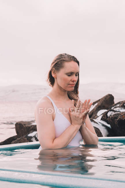 Young woman with closed eyes meditating in water of pool near rocks and cloudy sky — Stock Photo