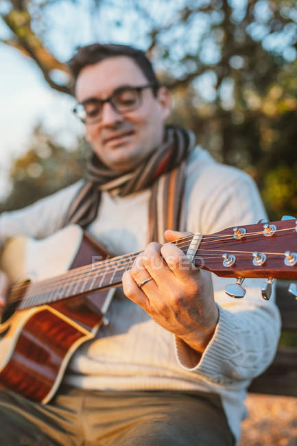 Casual man in eyeglasses playing guitar in countryside — Stock Photo