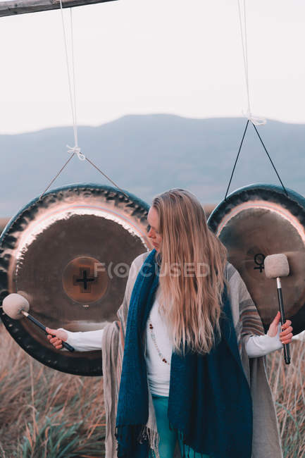 Young blond woman with mallets near ritual gongs between lands and hills — Stock Photo