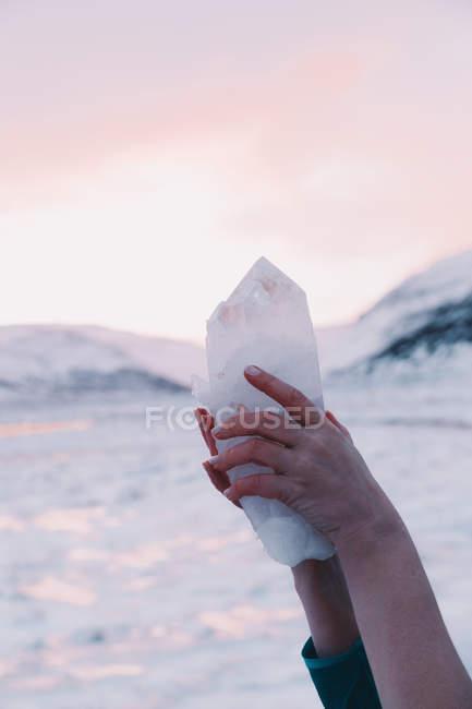 Руки женщины, держащей хрустальную скалу возле гор и розовое небо на размытом фоне — стоковое фото