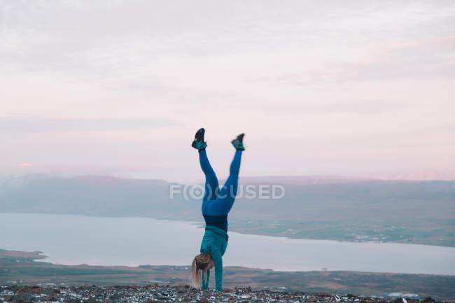 Donna bionda in piedi sulle mani sulla riva — Foto stock