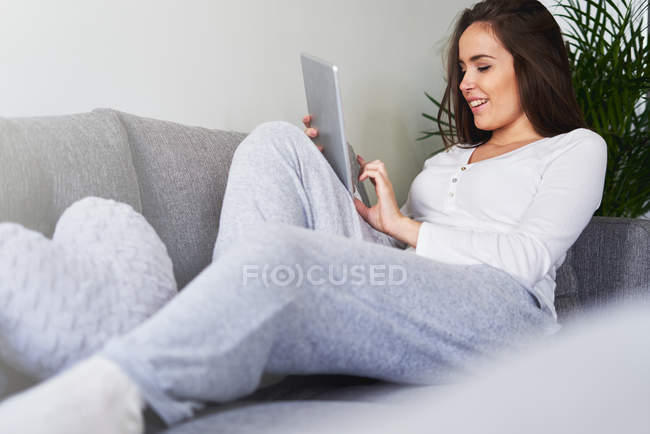 Young happy woman using digital tablet and resting on sofa at home — Stock Photo