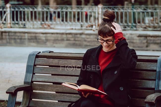 Молодая улыбающаяся элегантная женщина в очках читает книгу и сидит на скамейке в городском парке — стоковое фото