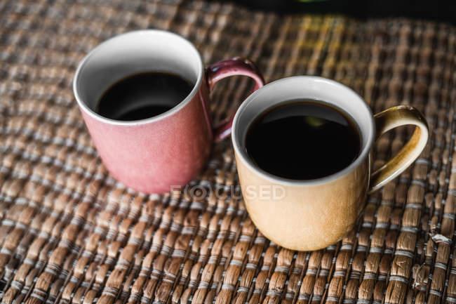 Satz von Tassen mit heißen Getränken auf Bambusmatte — Stockfoto