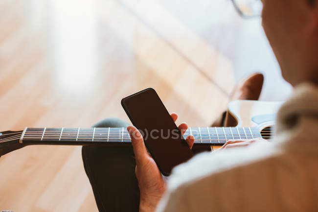 Hand of man playing guitar holding mobile phone — Stock Photo