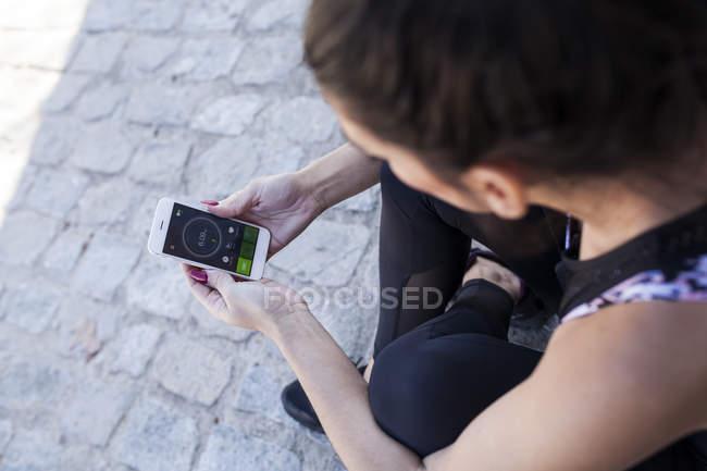 Крупный план брюнетки сидящей и проверяющей статистику тренировочного приложения — стоковое фото