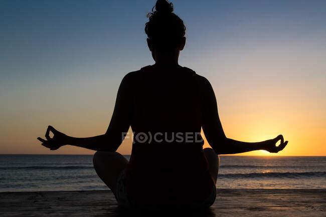 Вид сзади женщины, сидящей в позе лотоса и медитирующей на берегу у воды и голубого неба на закате — стоковое фото