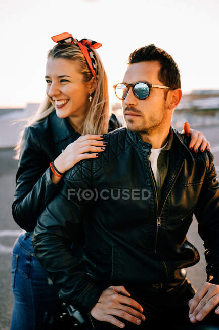 Lovely young woman smiling and looking away while sitting behind serious man on motorcycle — стокове фото