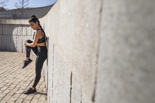 Брюнетка жінка розтягуючи м'язи сонячний день з гранітною стіною на фоні — стокове фото