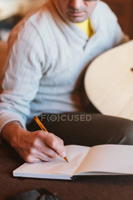 Крупний план музиканта з гітарним написанням в Блокноті — стокове фото