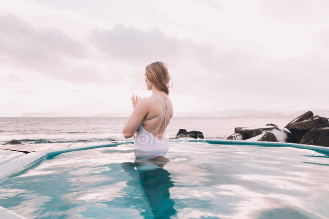 Young woman meditating in water of pool near rocks and cloudy sky — Foto stock