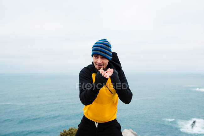 Adult bearded man in sportswear practicing punches during kickboxing workout near sea — Stock Photo