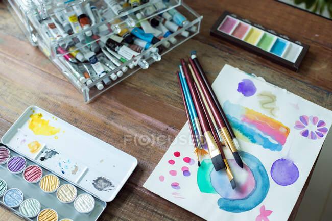 Fechar a paleta de cores da água e escovas — Fotografia de Stock