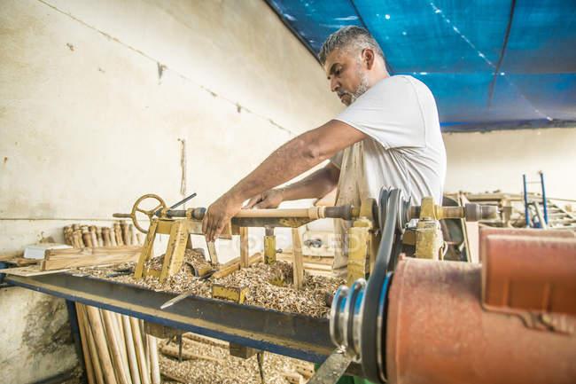 Älterer Mann mit Holzbearbeitungsmaschine in Werkstatt — Stockfoto