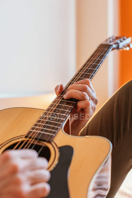 Hands of man playing guitar on bed — Stock Photo