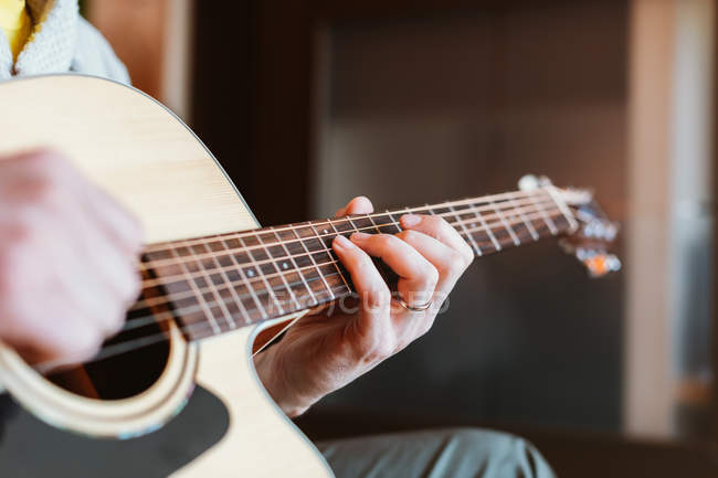 Hands of man playing guitar on blurred background — Stock Photo