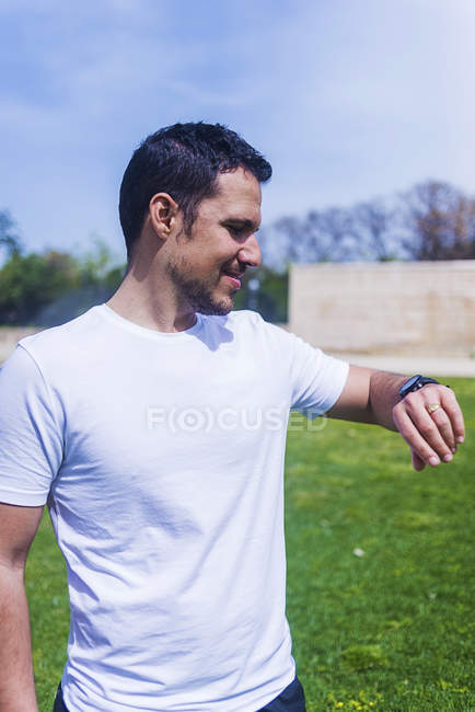 Young man in sportswear checking time on wrist watch in park in sunny day on blurred background — стоковое фото