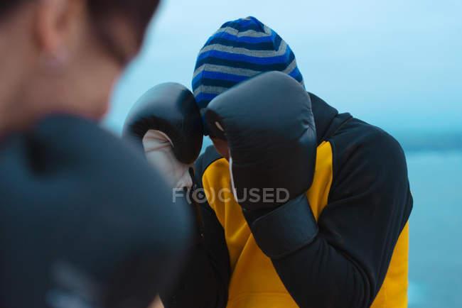 Крупный план мужчины и женщины в боксёрских перчатках, бьющих друг друга, стоя на берегу моря — стоковое фото
