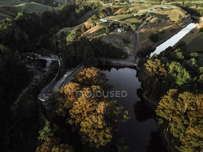 Río tranquilo cerca de bosques y colinas en verano - foto de stock