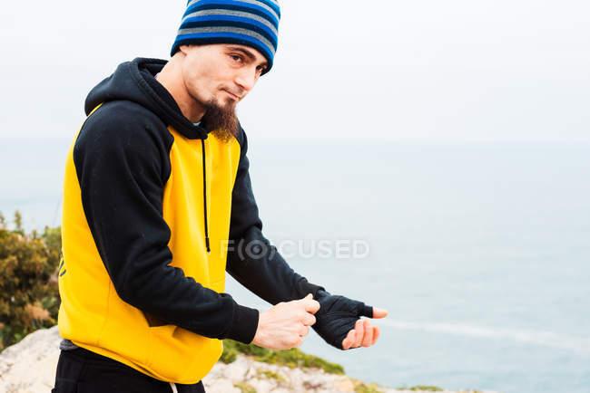 Взрослый мужчина с бородой обвязывает руку бинтом, стоя у моря во время тренировки по кикбоксингу на открытом воздухе — стоковое фото